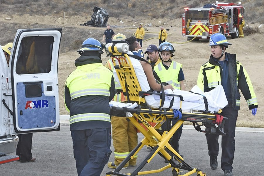 The occupant of a vehicle that rolled down a hill and caught fire (seen in the distance) is transported by ambulance from the Plum Canyon area on Saturday. Dan Watson/The Signal