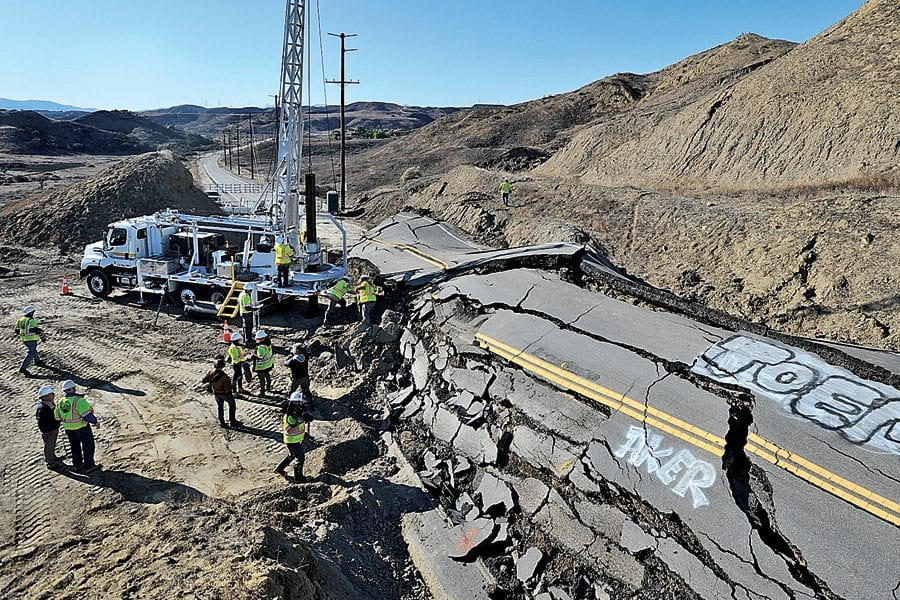 Los Angeles County Public Works workers drill a hole into the earth next to Vasquez Canyon Road as they prepare to lower engineering geologist Karin Burger into the hole to investigate why the road began to slide in late November. KATHARINE LOTZE/SIgnal. 12152015